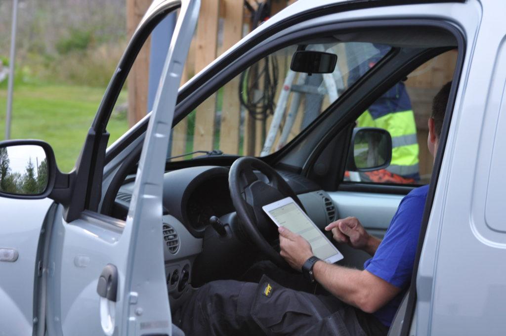Håndverker fører regnskap i bilen